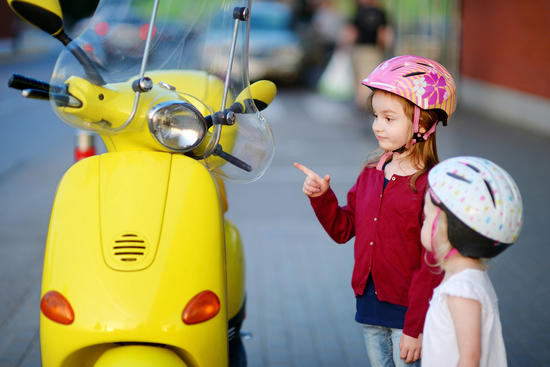 Two very curious little girls and a yellow motorcycle